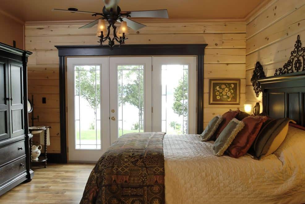 Photo of a Confederation Log & Timber Frame bedroom with large french doors.