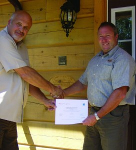 Rick Kinsmasn of Confederation Log & Timber Frame is presented with Energy Star certification