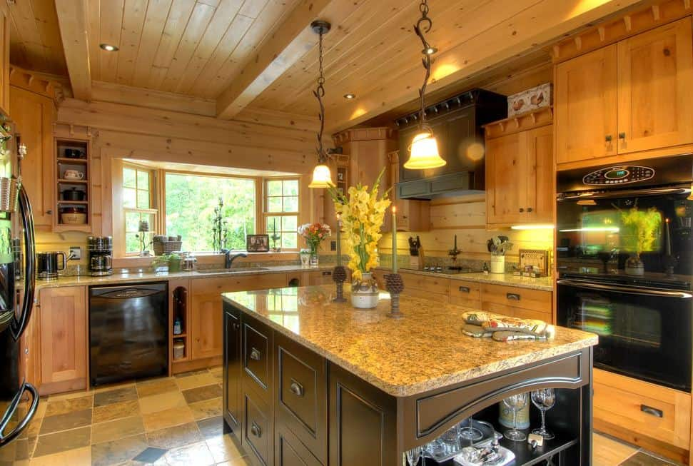 Photo of a kitchen with granite counters and black appliances