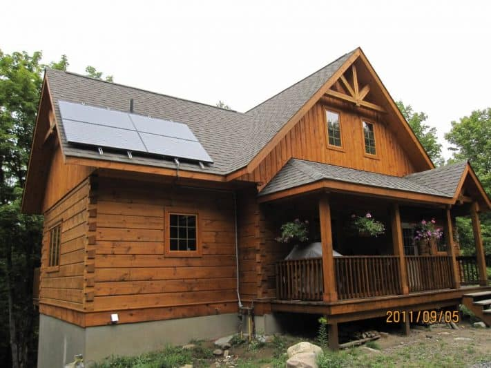 Off the grid log home with solar panels.